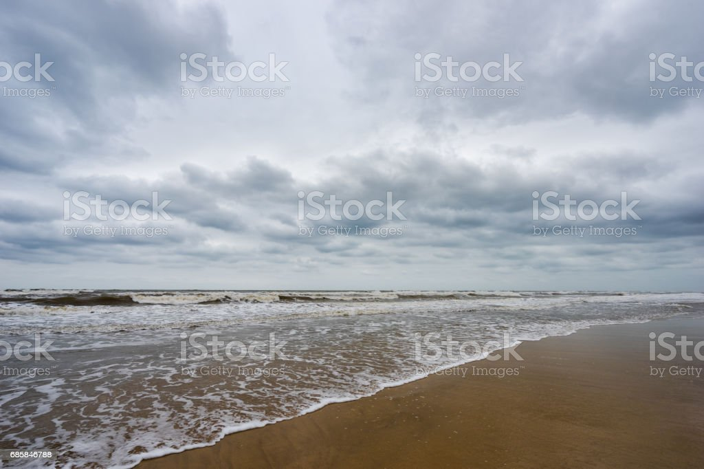 Sand beach, blue sea and white bubble wave in cloudy day stock photo
