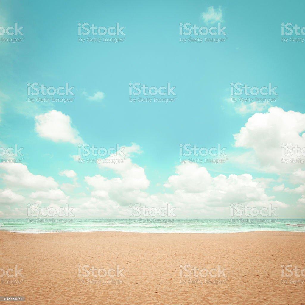 Sand beach, clouds and blue sky - retro lighting effect stock photo