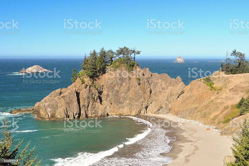 sand beach in rocky cove with ocean beyond stock photo