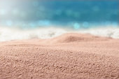 Sand beach with blurred sea and sunny background, close up.