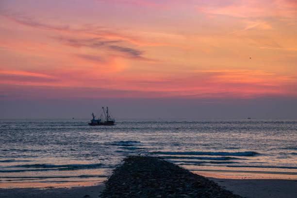 sandstrand sonnenuntergang blick auf insel norderney, reise deutschland - urlaub norderney stock-fotos und bilder