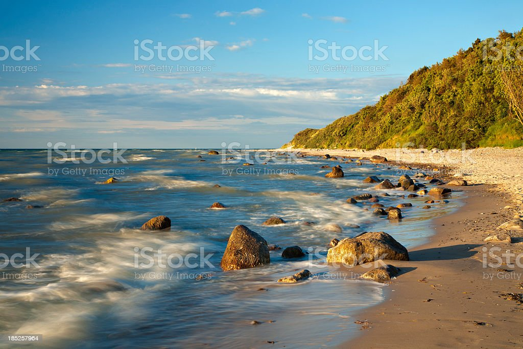 Sand Beach with Boulders in Warm Light of Setting Sun stock photo