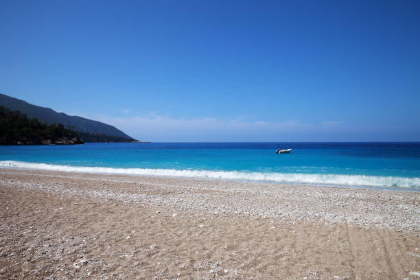 Sand beach with pebble stones and beautiful blue sea Sand beach with pebble stones and beautiful blue sea at warm sunny summer day. Mediterranean sea, Turkey. cusp stock pictures, royalty-free photos & images