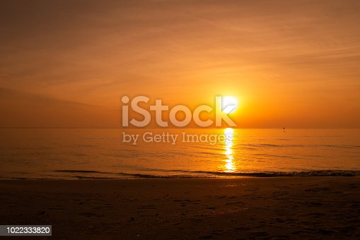 Sand beach with sunset or sunrise at the horizon line