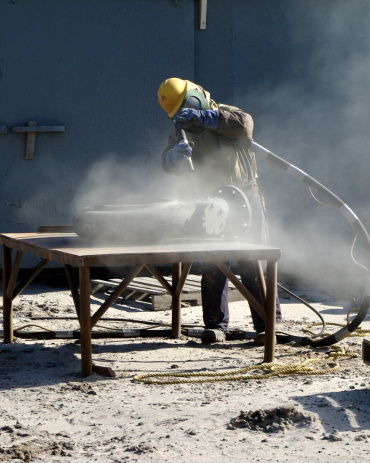 Man sand blasting a section of piping that belongs to a fishing boat. He is wearing protective gear to do his job.
