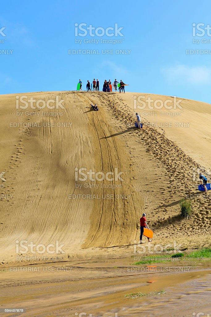 Sand boarding at Cape Reinga sand dunes, New Zealand stock photo