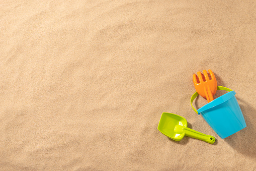 Top view of a blue sand bucket with a green pale and a orange shovel on a beach sand background. All the objects are at the lower left corner leaving a useful copy space at the left and at the top of the image. Studio shot taken with Canon EOS 6D Mark II and Canon EF 24-105 mm f/4L