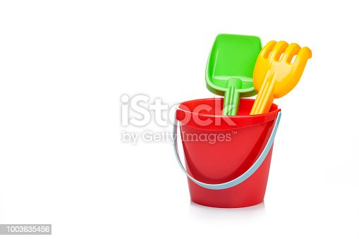 Front view of a sand bucket, pail and shovel taken on reflective white background. The objects are grouped at the right of an horizontal frame leaving useful copy space for text and/or logo at the center-left. Predominant colors are red and white, but also are present green and yellow. High key DSRL studio photo taken with Canon EOS 5D Mk II and Canon EF 100mm f/2.8L Macro IS USM.