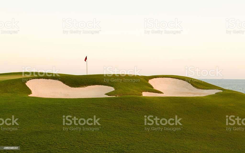 Red flag of golf hole above sand trap or bunker on beautiful ocean...
