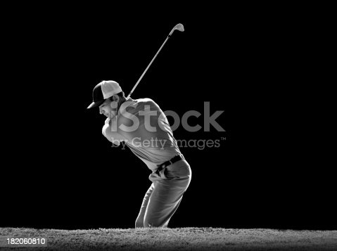 A B&W image of a golfer hitting out of a sand trap.