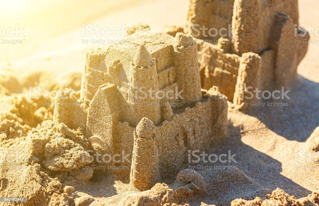 Sand castle tower. Child play and vacation concept. blur, depth of field, sunlight background stock photo