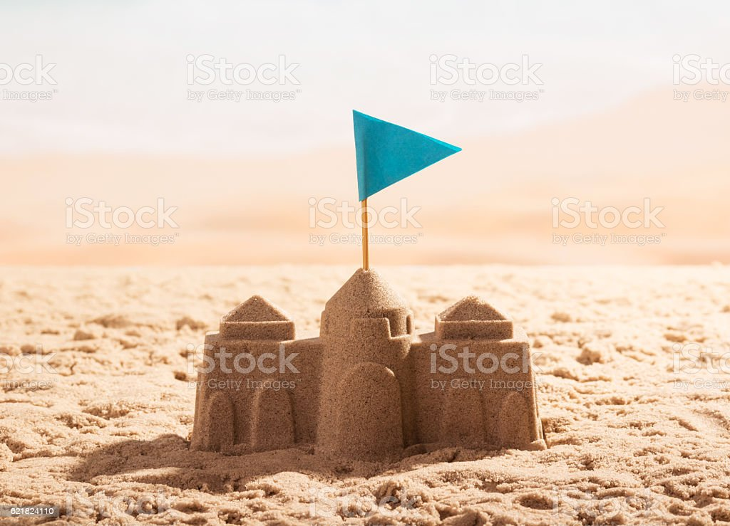Sand castle with flag on the sea shore. – Foto