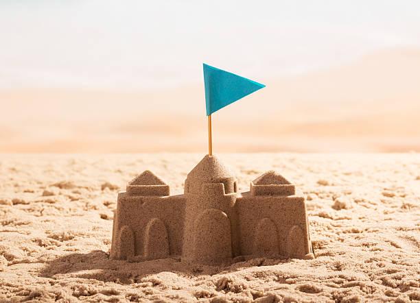 sand castle with flag on the sea shore. - chateau de sable photos et images de collection