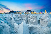 Sand castles with the lights of the Boardwalk in the background.