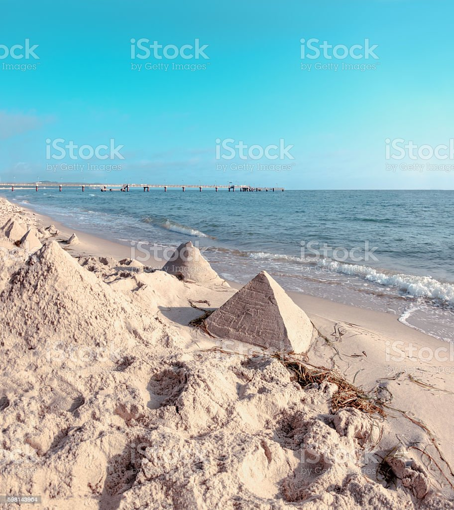 Sand castles in shape of pyramides on Baltic Sea stock photo