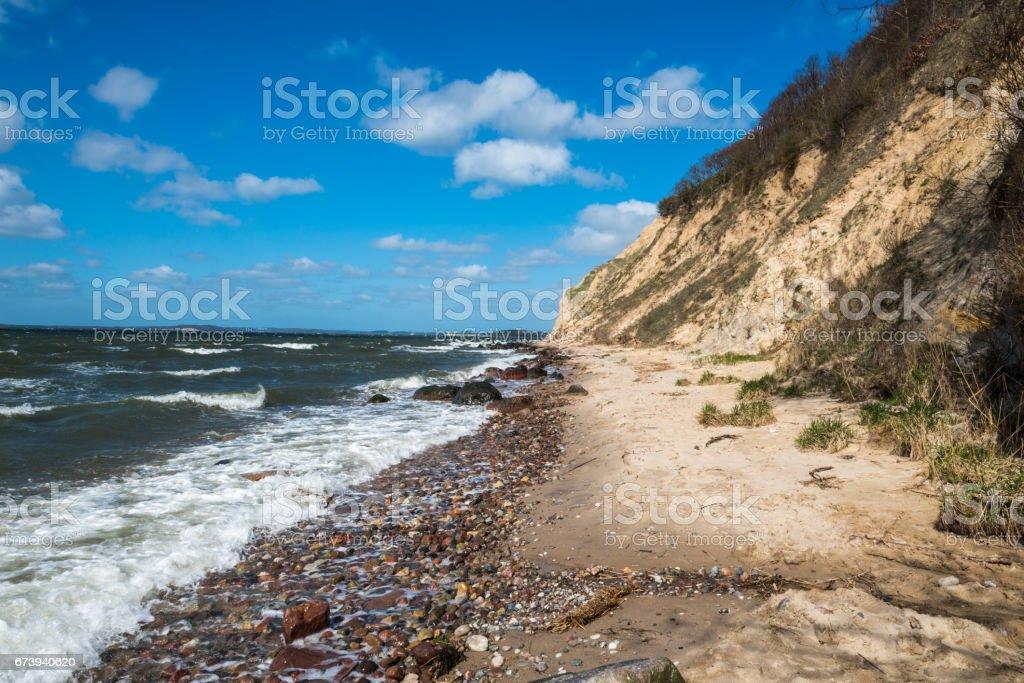 sand cliff beach at baltic sea - boulder rock, stone, pebbles stock photo