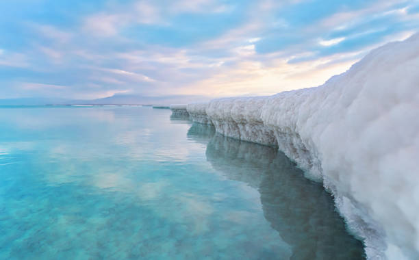 Sand completely covered with crystalline salt looks like ice or snow on shore of Dead Sea, turquoise blue water near, sky colored with morning sun distance - typical scenery at Ein Bokek beach, Israel stock photo