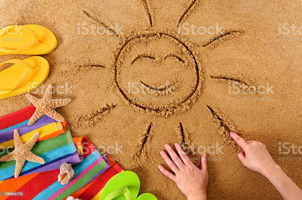 Sand Drawing of a happy sun, with sandals, stars and a towel royalty-free stock photo