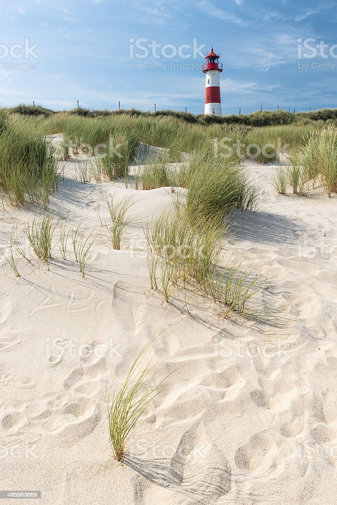 Sand dune and lighthouse on background. stock photo