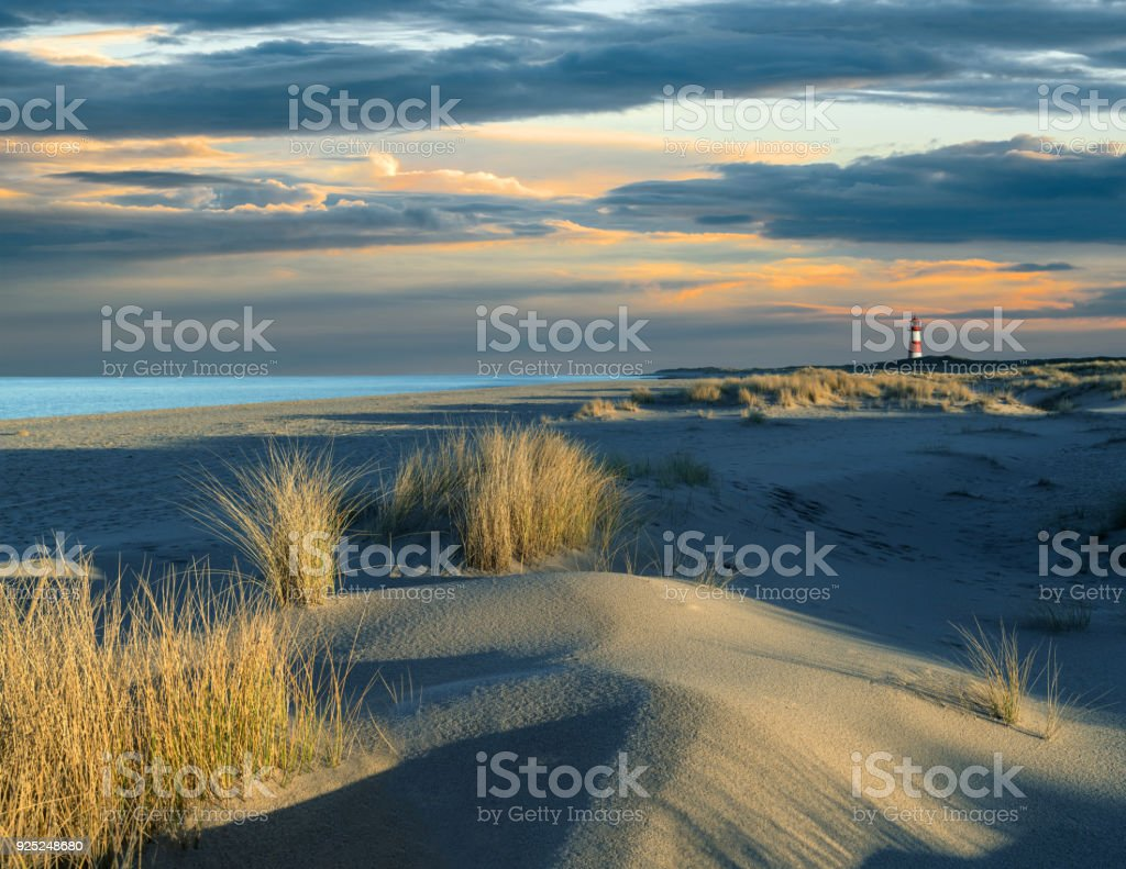 Sand dune and lighthouse on island Sylt at sunset with majestic cloudscape stock photo