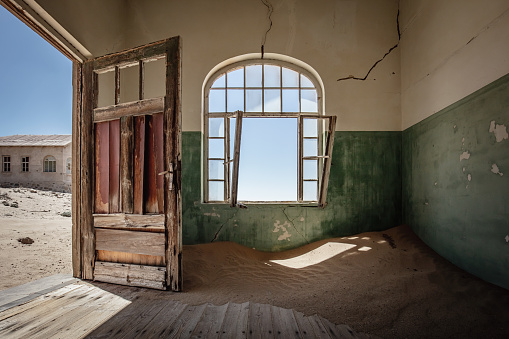 Sand Dune filling up abandoned Ghost Town House through broken window. Lüderitz, Namibia, Africa