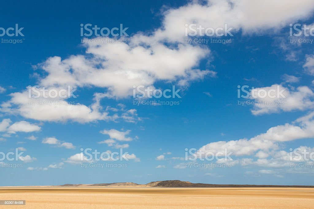 Sand dune with cloudy blue sky in La Guajira, Colombia stock photo