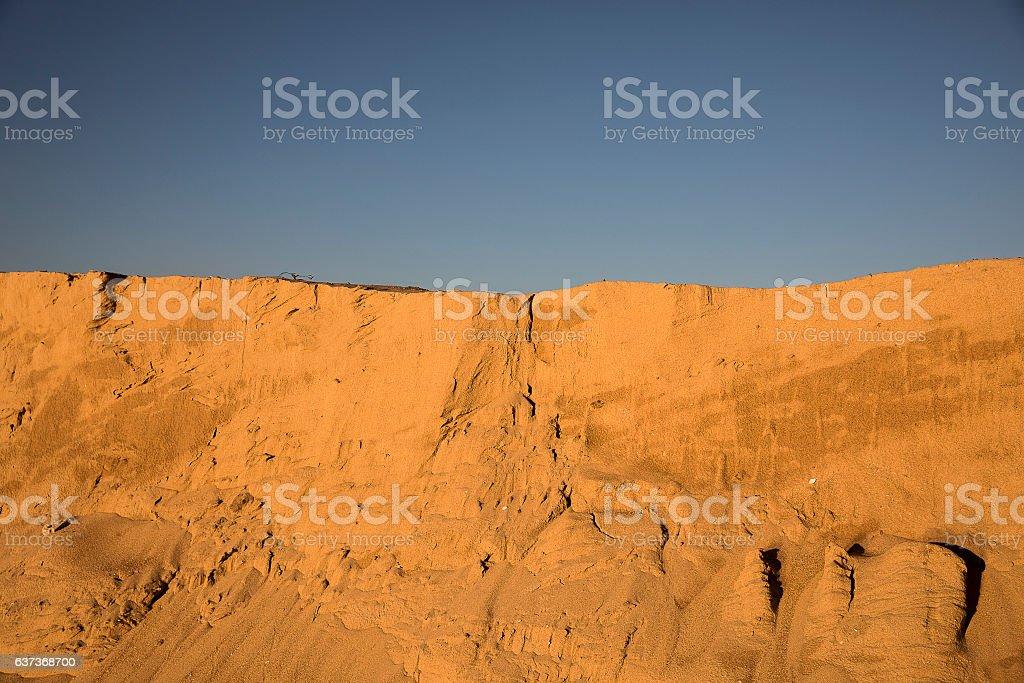 sand dune with orange sunset winter light and blue sky stock photo