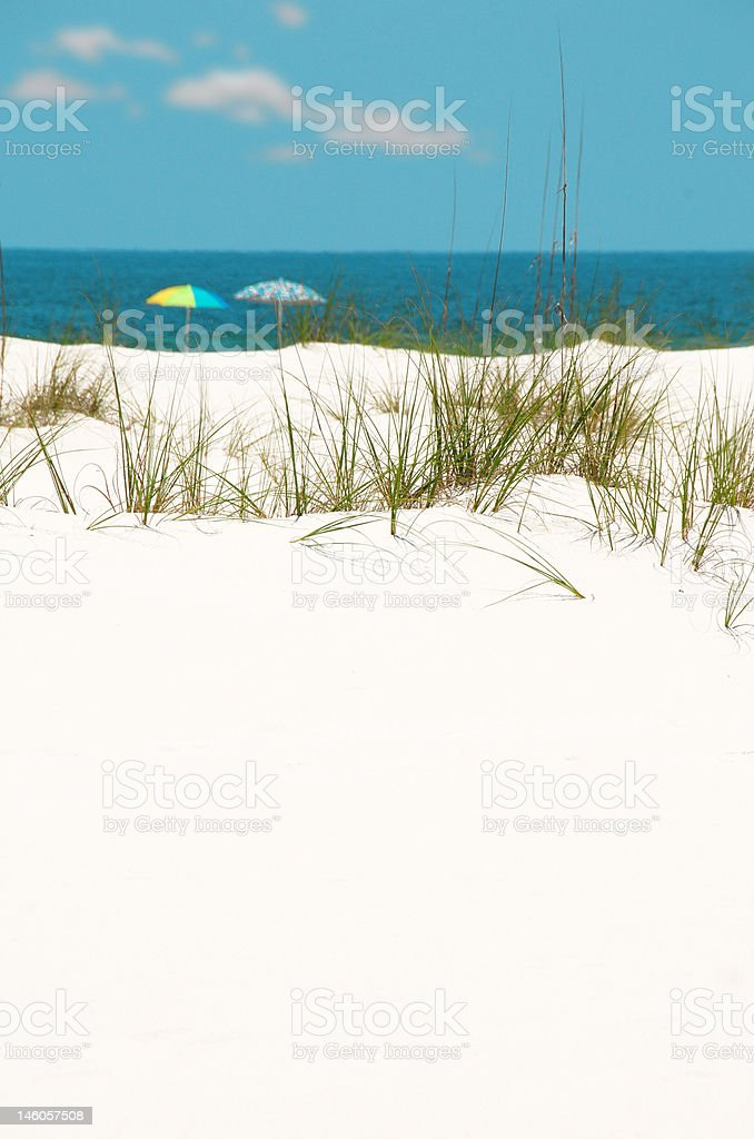 Sand Dune with Umbrellas in Distance stock photo