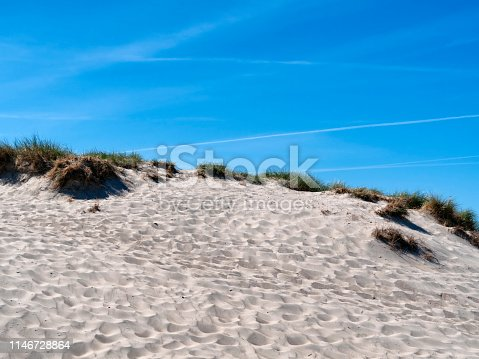 Sand dunes and marram grass at Warnemünde in Mecklenburg-Vorpommern on the Baltic Sea coast of northern Germany on a sunny day in springtime with blue sky criss-crossed by vapour trails. The dunes are covered in footprints and wind-ripples.