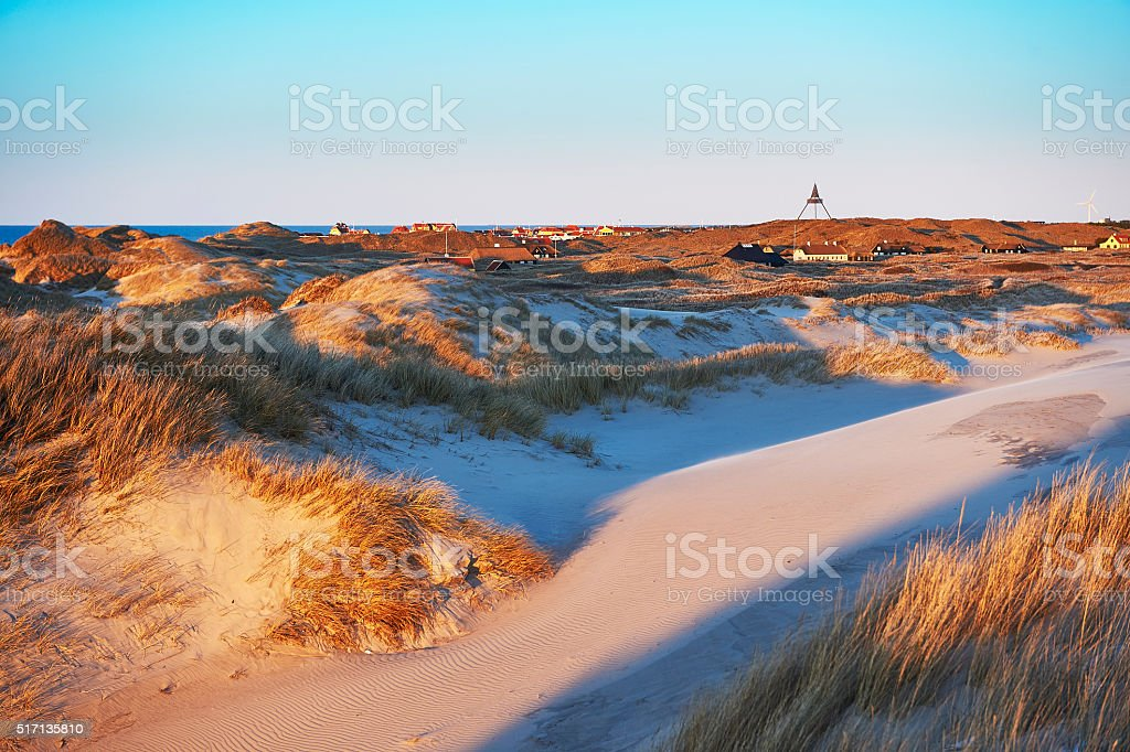 Sand dunes at the sea with setting sun in Skagen stock photo