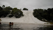 salvador, bahia / brazil - september 7, 2011: people are seen in a lagoon next to a sand dune in the region of Itapua in the city of Salvador.