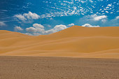 Cloudy sky and sand dunes in the Algeria