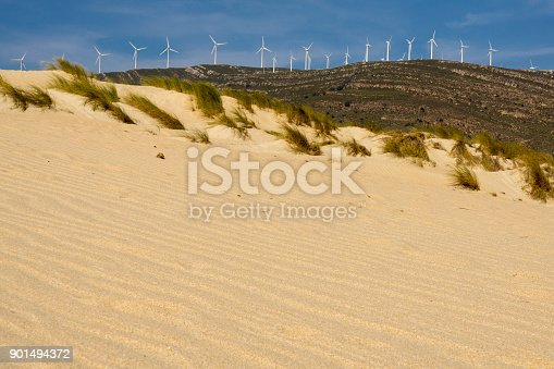 Sand dunes on the beach against the background of mountains. Tarifa. Spain.