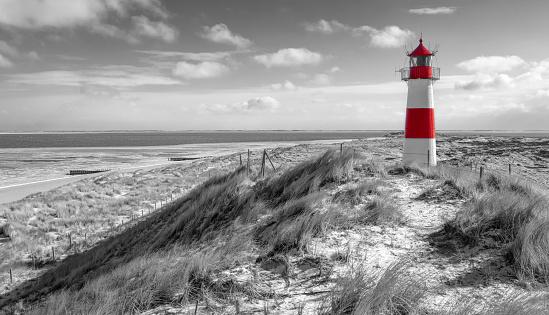 Sand dunes with lighthouse at Ellenbogen on island Sylt, Schleswig-Holstein, Germany.