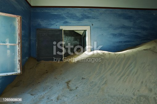 Sand filled blue room at Kohlmanshop, a former diamond mining town in southern Namibia