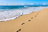footprints and surf on tropical beach, Kauai, Hawaii