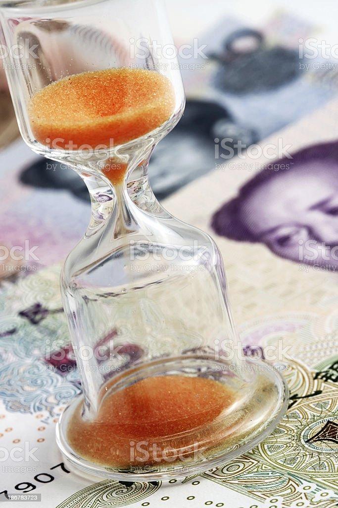 Sand glass on Chinese yuan stock photo