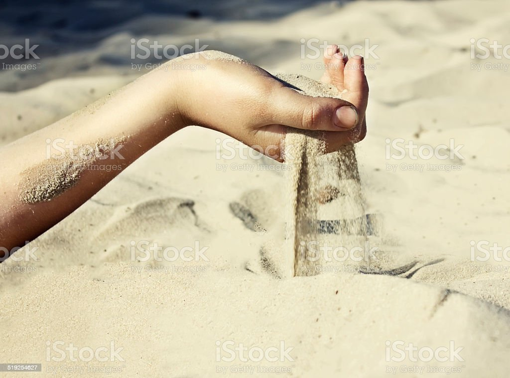 Sand is pouring through his fingers stock photo