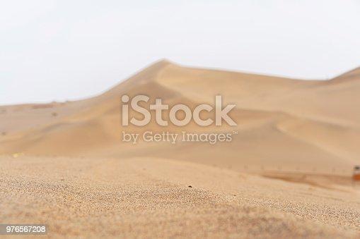 Sand mountain range in desert under blue sky