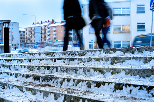 Ice cold stair covered by snow and ice. Sand is added to prevent slipping.