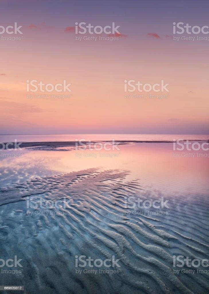Sand on the seashore during sunset stock photo