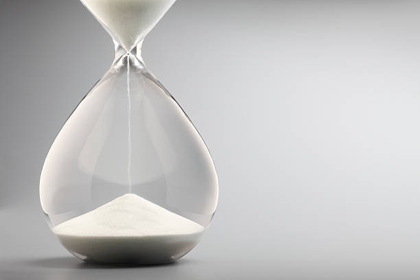 sand pouring into bottom of hourglass on gray background - deadline stock pictures, royalty-free photos & images
