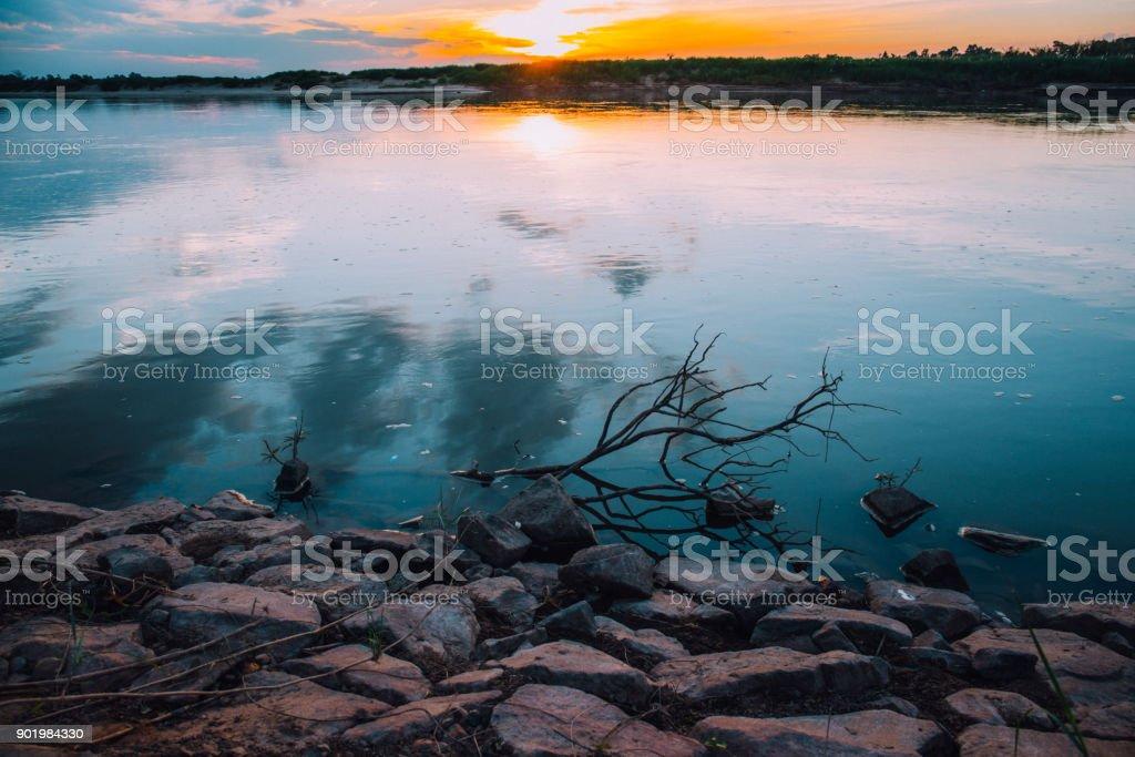 pedra de areia com ramo de madeira seca no rio com o céu do sol em Tom vintage na zona rural - foto de acervo