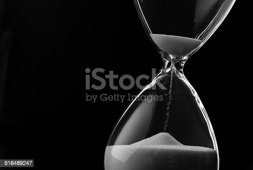 istock Sand running through the bulbs of an hourglass 516489247