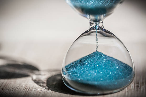 Sand running through the bulbs of an hourglass Sand running through the bulbs of an hourglass measuring the passing time in a countdown to a deadline, on a bright wooden background with copy space. timer stock pictures, royalty-free photos & images