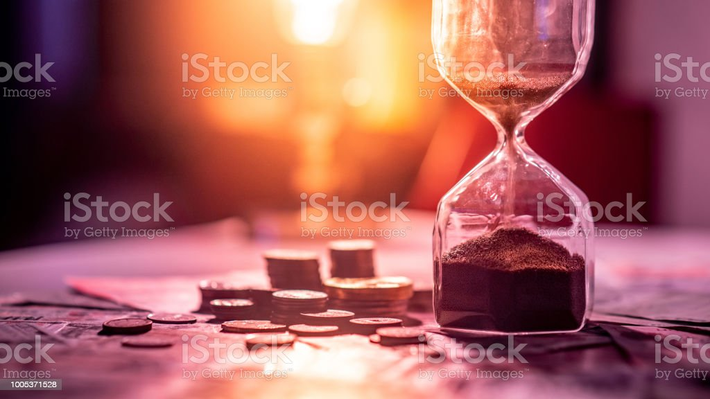 Sand running through the shape of hourglass on table with banknotes and coins of international currency. Time investment and retirement saving. Urgency countdown timer for business deadline concept - Zbiór zdjęć royalty-free (Bank)