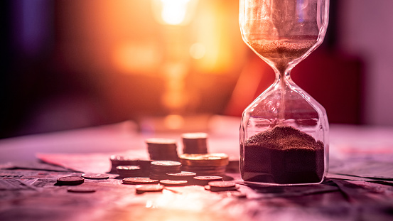 Sand Running Through The Shape Of Hourglass On Table With Banknotes And Coins Of International Currency Time Investment And Retirement Saving Urgency Countdown Timer For Business Deadline Concept - zdjęcia stockowe i więcej obrazów Bank