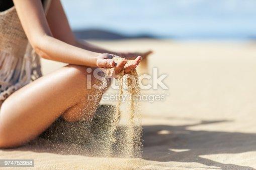 Sand running through woman hands in desert. Time running concept