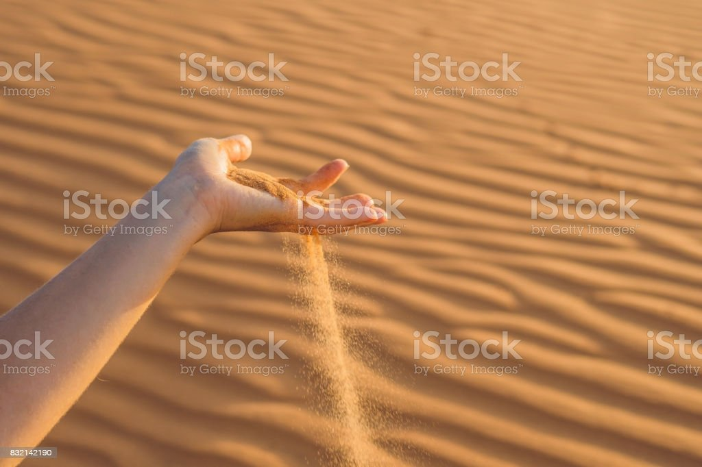 Sand slipping through the fingers of a woman's hand in the desert stock photo