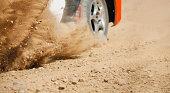 Sand splashing from rally racing car on dirt track.